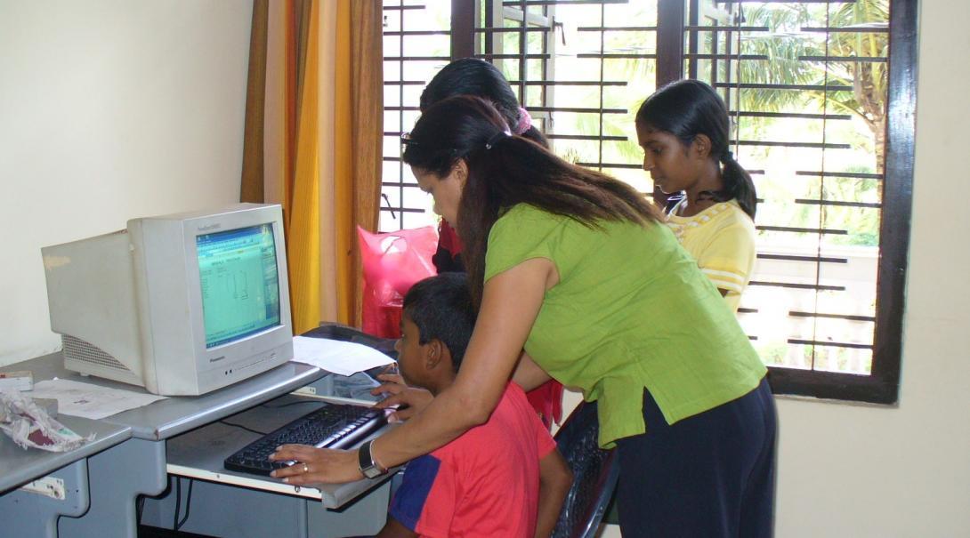 Dos alumnos realizan un ejercicio en el computador con la ayuda de su profesora voluntaria de informática.